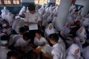 Siswa mengerjakan soal ujian akhir semester (UAS) mata pelajaran Matematika di kelas darurat Masjid Jami' Arjosari, di Pacitan, Jawa Timur, Selasa (5/12/2017). Sebanyak 760 siswa SMPN Arjosari mengikuti UAS di dua masjid desa karena sekolah mereka rusak diterjang banjir beberapa waktu lalu. (ANTARA FOTO)