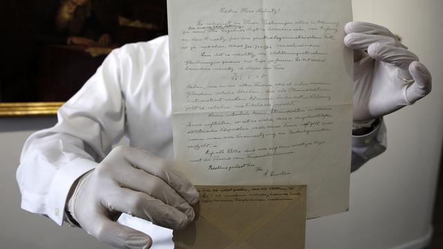 """Petugas menunjukkan surat rumusan """"Tahap Ketiga Teori Relativitas"""" yang ditulis Albert Einstein di rumah lelang Winner, Selasa (6/3). Isi surat mencakup catatan tambahan yang ditulis di balik amplop yang memperkuat pemikiran Einstein"""