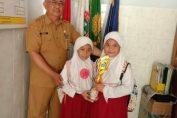 Foto Kepala Sekolah Drs. Purnomo M.Pd dan siswa juara 1 loimba 3M