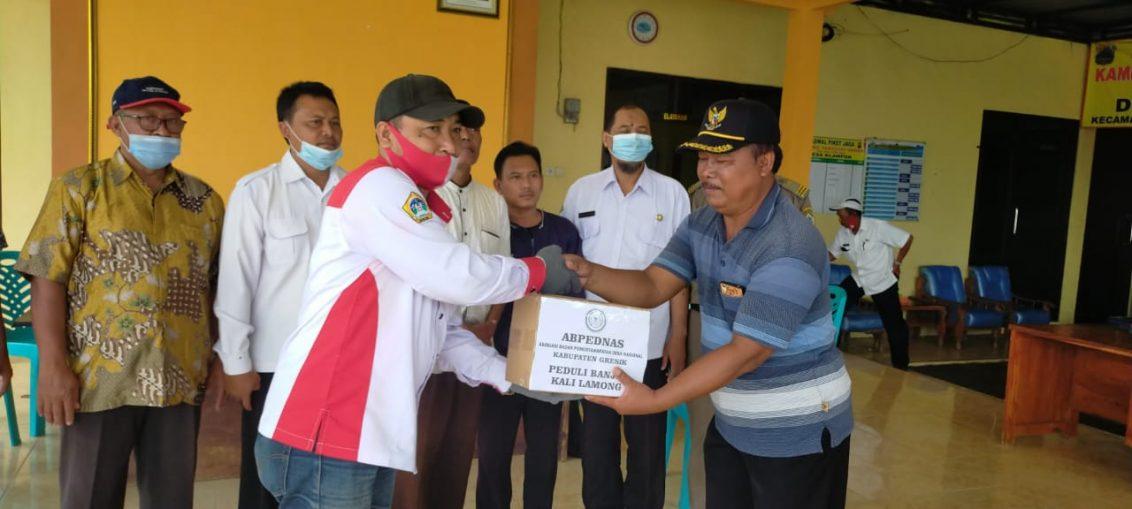 Ketua DPC Abpednas Gresik saat menyerahkan bantuan kepada warga terdampak banjir Kali Lamong di Kecamatan Benjeng Kabupaten Gresik.